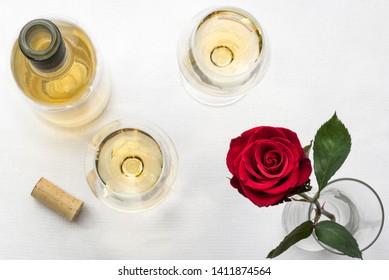 White Wine Bottle, Stemware, and Rose on White Linen