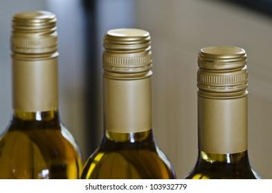 Weiße Weinflaschen mit Stelvin-Kapseln und enger Fokus auf die nächste Flasche