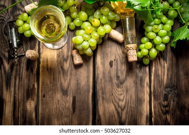 White wine with branches of white grapes. On a wooden table.