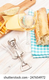 White wine, cheese and bread on white wooden table background