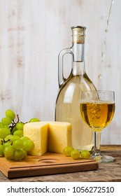 White wine, cheese and grapes on an old wooden table. Wine is poured in glass