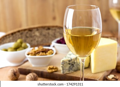 White Wine, cheese, nuts, olives, dried fruit, bread and garlic on wooden table