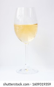 White wine in cristal glass, pure chardonnay on white background, yellow shade of transparent drink for restaurant and party bar, luxury alcohol