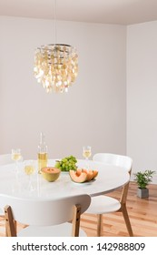 White wine and fruits on a table. Room decorated with beautiful chandelier.