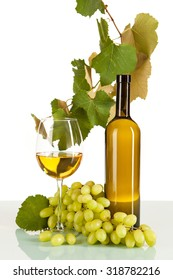 White wine in glass and bottle with bunch of grapes