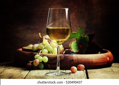 White wine in a glass with fall grapes, old wooden background, selective focus