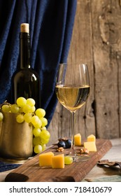 White wine in glass goblet green yellow grapes, bottle and pottery jar, cheese platter wooden board, blue curtain with drapes, vintage old tavern still life, family winery eco farm, wooden background
