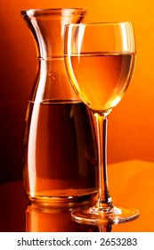 White wine, wine glass and wine jug. Placed on glass table. Warm color background light.