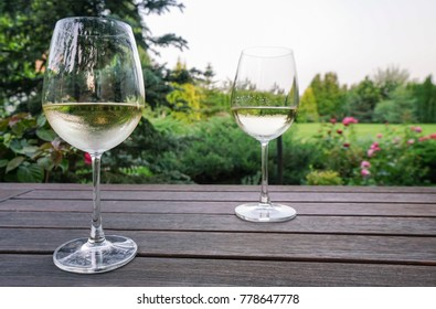 White wine glasses on wooden table at garden in summer