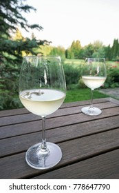 White wine glasses on wooden table