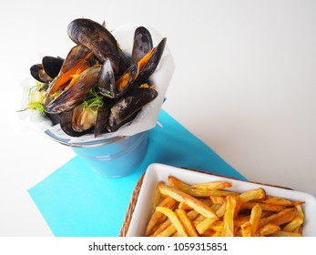 "White wine open mussels in a bucket, french ""marinière"", with homemade golden french fries on a plate, on white and blue background"