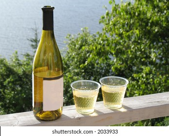 White wine and plastic glasses on deck railing overlooking water.