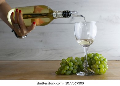 White wine pouring from bottle with chiller stick and into a glass