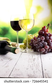 White wine and red wine in a glass with fall grapes, white wooden background.