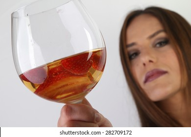 white wine and strawberries in a crystal glass - a beautiful young smiling brunette with large breasts in a white sexy silk peignoir