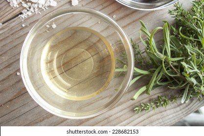 White wine vinegar, near thyme and rock salt. On wooden background