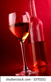 White wine.Wine glass and wine bottle.Placed on glass surface with small mirror reflection.Warm background light.