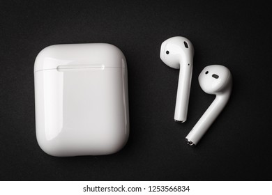 White wireless bluetooth earphones or headphones and plastic case or box for storage and charging on black background, close up