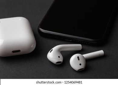 White wireless bluetooth earphones or headphones, plastic case or box for storage and charging and smartphone on black background, close up