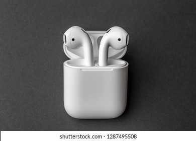 White wireless bluetooth earphones or headphones and white box for storage and charging on dark grey background, close up