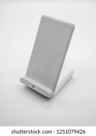 White wireless charger stand with modern design isolated on white background.