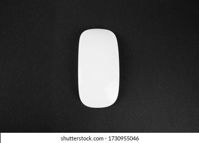 White wireless computer mouse on black background. Modern sleek design for websites and banners.