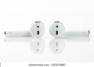 White wireless earphones on white background close-up. Modern handsfree. Technologies. Electronics.