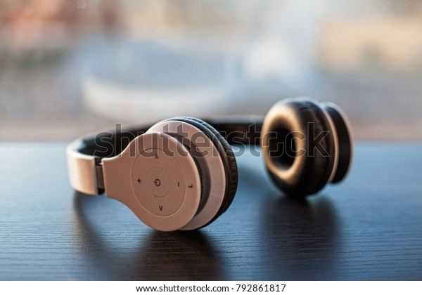 White wireless headphones placed on laminated dark wooden surface on a blurred window glass background colored by sunlight.