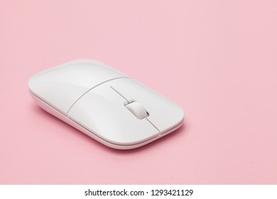 White wireless optical mouse with a wheel on a pink background. Modern concept for the Internet web site. Free space for input text, image, and logo. Mockup