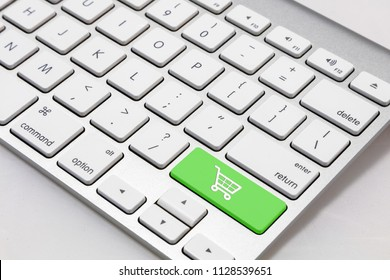 "White wireless  style keyboard with green ""shopping cart"" symbol key"