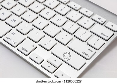 """White wireless style keyboard with a white """"recycle"""" symbol key."""