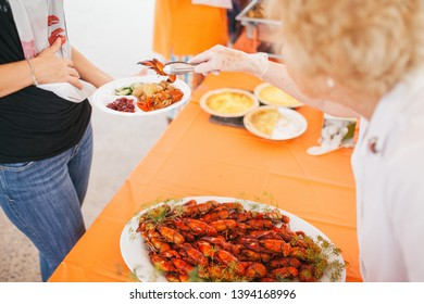 White woman being served crayfish during a Swedish crayfish party