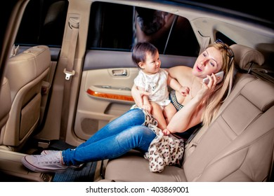 White woman with a child of one year old in the light leather car interior have conversation by phone