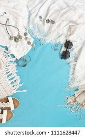 White woman clothes and accessories on blue background. Summer romantic outfit, top view point, flat lay.