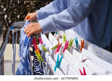 White woman hanging laundry clothes outside on a sunny day
