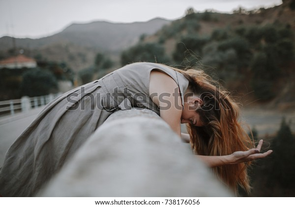 White woman leaning out in a bridge while wind moves her hair in a mountain road.