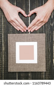 White woman making heart gesture with hands near family photo album isolated on wooden brown background. Overhead vertical shot.