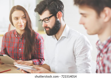 White woman and men using pad tablet mobile device and doing paperwork at office desk. Teamwork and technology concept