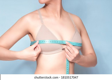 White woman with nude bra with a tape measure or measurement (Meter) measuring the middle part of the bust (Nipple) in a blue studio background