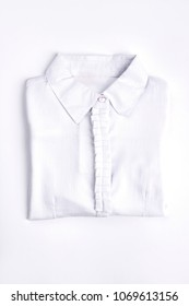 White woman shirt on white background. New folded cotton blouse for school girls. New collection of modern cotton shirts for girls.