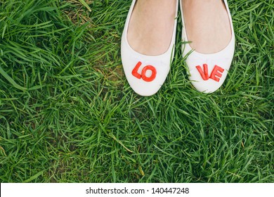 White woman shoes with red LOVE letters, green grass background, top perspective, before wedding, engagement photo, vintage color