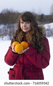 white woman stay and hold orange fruits winter outdoors