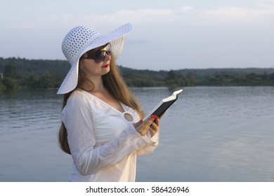white woman in sun hat read paper book on beach concept
