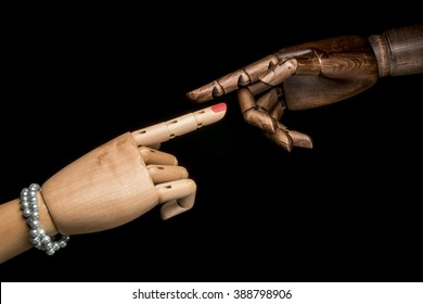 A white woman's hand and a hand of black man pointing forefinger toward one another. On black background.