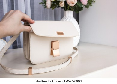 White women's leather bag with on a white table with a vase, flowers and a clock in the background
