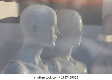 white women's mannequins stand in a display case without clothes. High quality photo