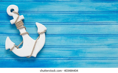 A white wood anchor on a blue background in business card proportions