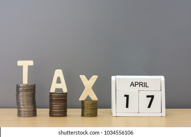 White wood block calendar for April 17. Wood tax and money coin stack on wooden table background. Tax Day 2018 takes place on April 17,2018