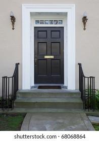 White wood bordered black door of beige stucco house