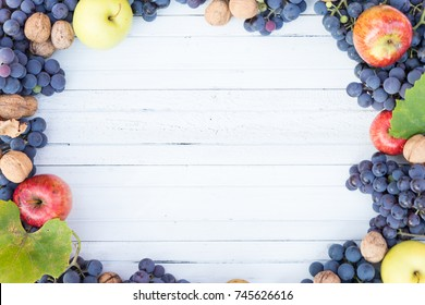 White wood copyspace with autumn fruits frame like apples, grapes and wallnuts as fall advertising concept